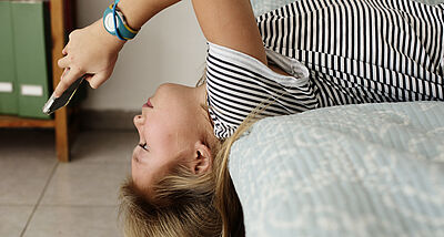 Girl lying upside down on bed looking at smartphone