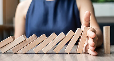 Businesswoman hand Stopping Falling wooden Dominoes. Business, Risk Management, Solution and strategy Concepts
