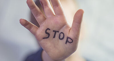 Concept of domestic violence and child abusement. A little girl shows her hand with the word STOP written on it. Children violence.